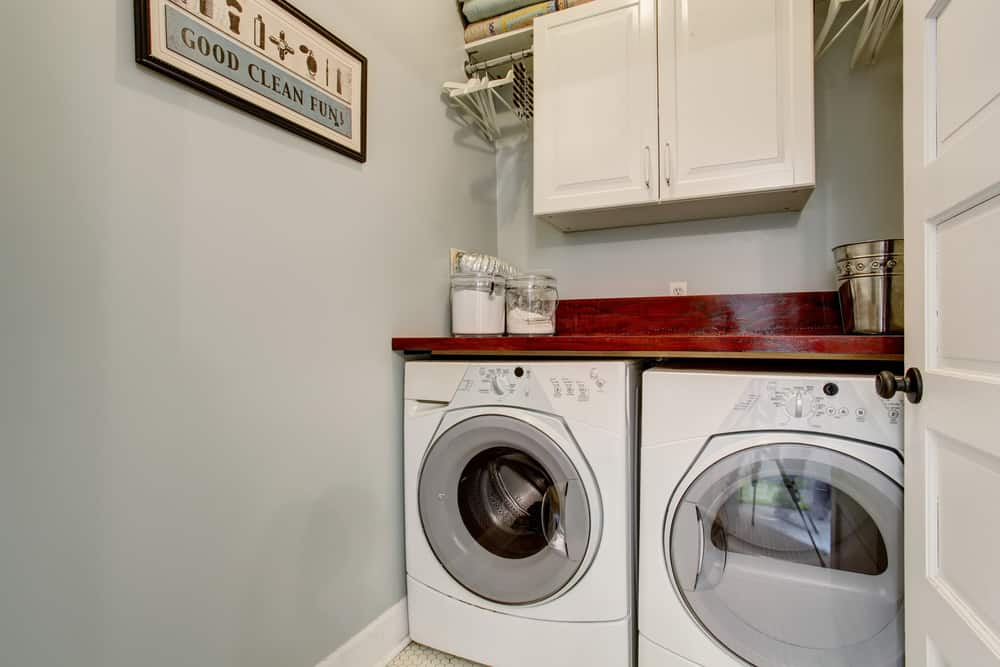 A washer and dryer combo with stylish red counter and white cabinetry just above.