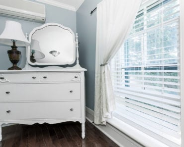 White dresser with mirror in bedroom