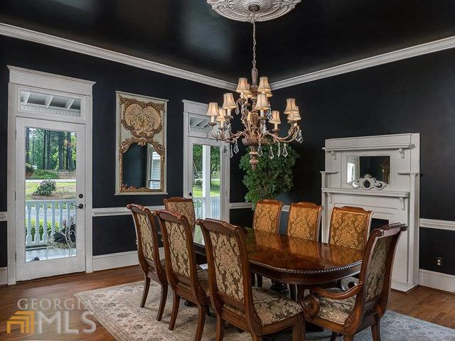 Elegant black dining room contrasted with a white fireplace that faces the rich wood dining table and classy floral chairs illuminated by a vintage chandelier.