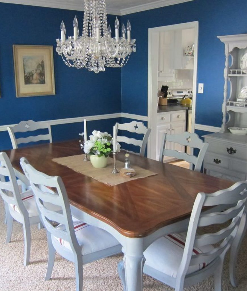 Farmhouse blue dining room with rectangular wooden table and chandelier.