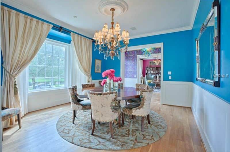 Gorgeous dining room styled with a huge mirror mounted on the blue wall above white wainscoting. It has an octagonal dining table surrounded with wingback chairs that sit on a round patterned rug.
