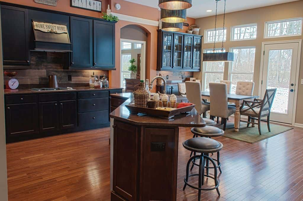 Warm kitchen with black cabinetry and a wooden breakfast island paired with round bar stools. It includes a wooden dining table with white tufted and cushioned accent chairs.