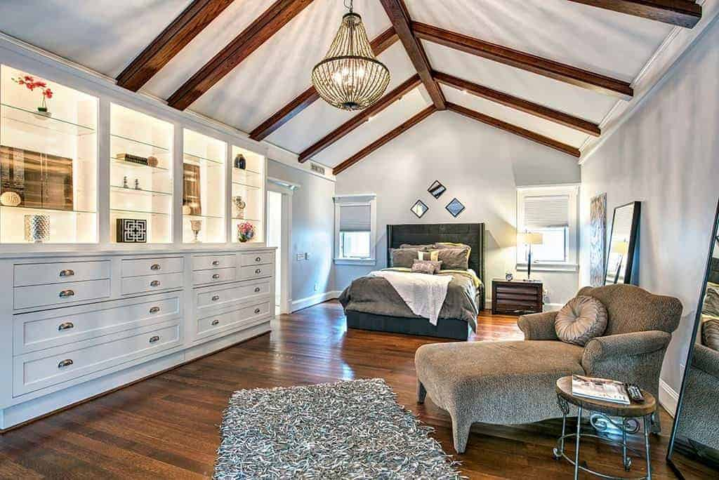 Large primary bedroom with high ceilings, wood beams, chandelier fixture and transitional wooden floor.