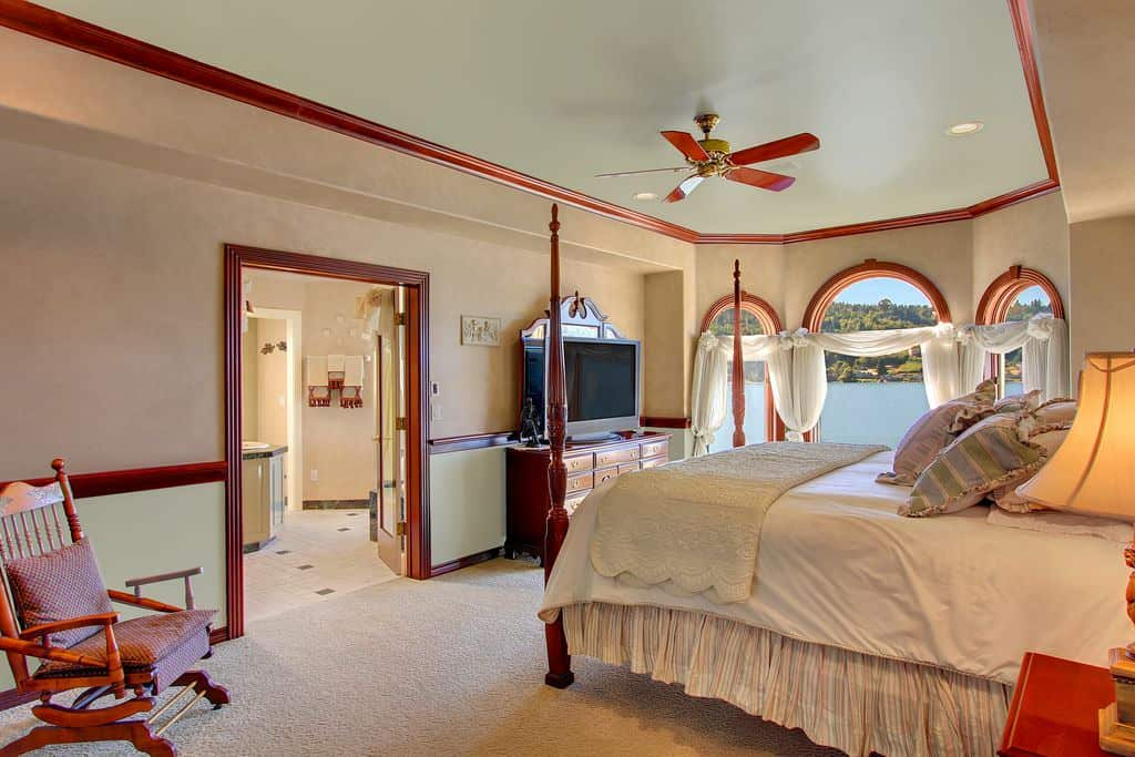 A fancy large bedroom featuring carpet flooring and a tray ceiling. The room has its own bathroom.
