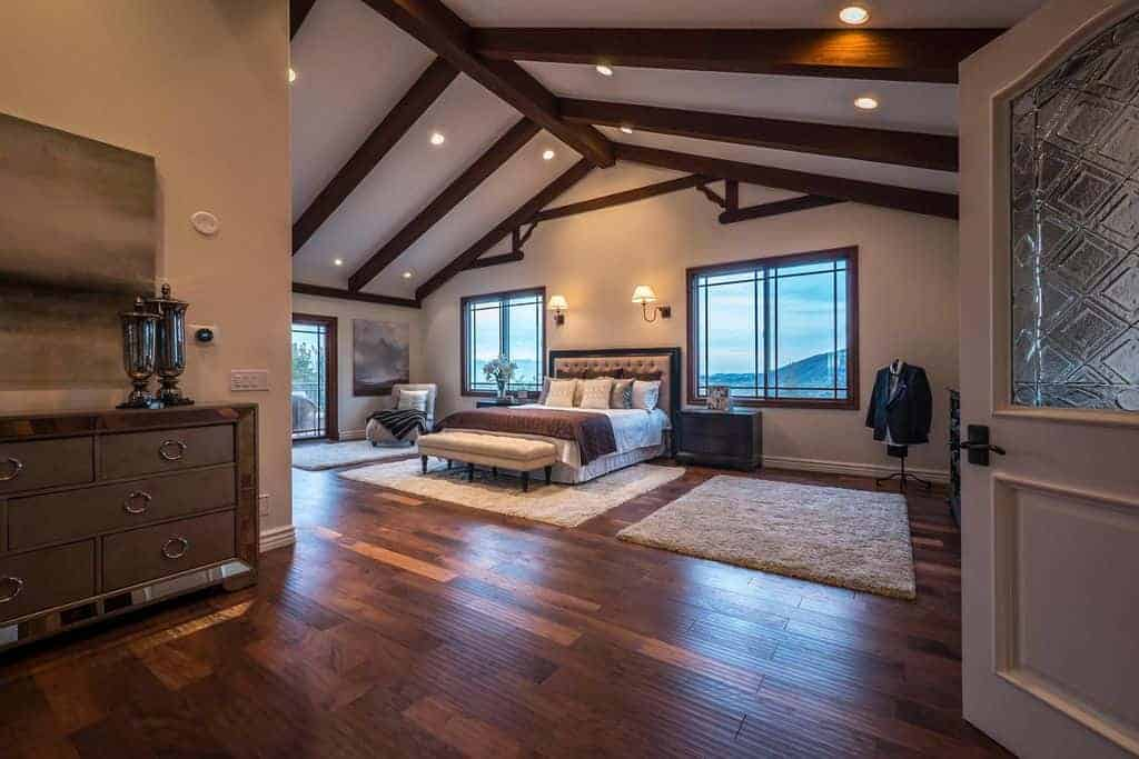 Beautiful wood beams emphasized this rustic and cozy bedroom featuring traditional ornaments and wooden floors.