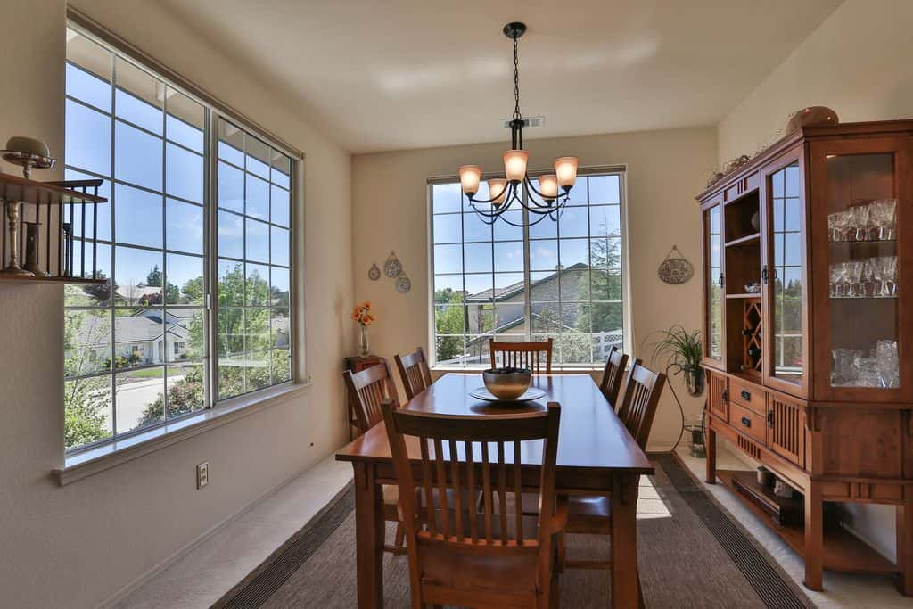 Craftsman dining room with chandelier and wide glass window.