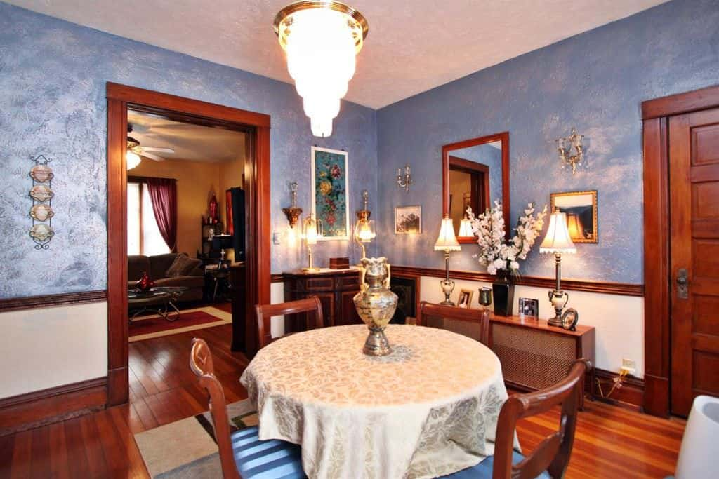 Craftsman Blue Dining Room With Elegant Set Of Lights And Hardwood Floors.  Source: Zillow Digs