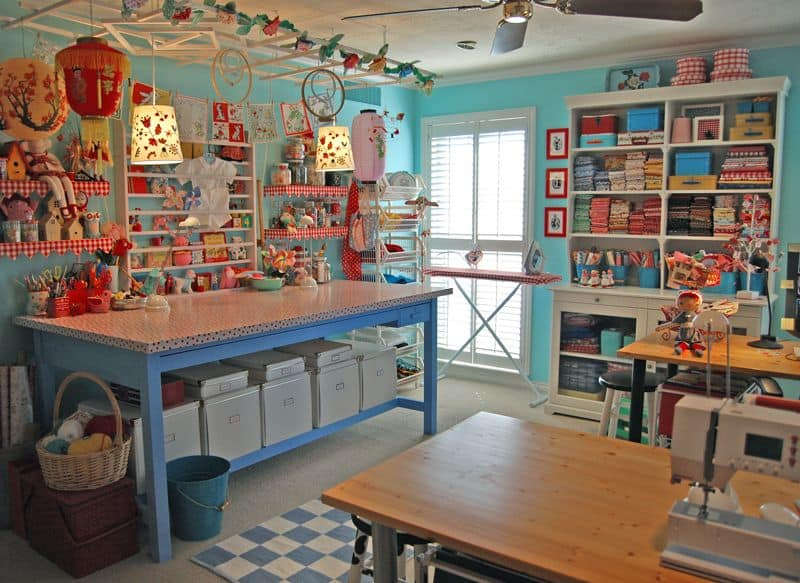 Eclectic green craft room with built-in shelves and carpet flooring.