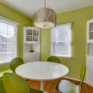 Green contemporary dining room with hardwood floor and pendant light.