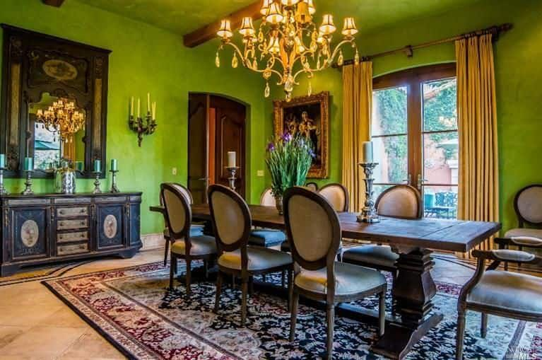 Green dining area lighted by a lovely chandelier that hung over a wooden dining table with round back chairs. It sits on a vintage rug over tiled flooring.