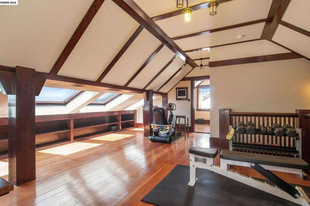 Craftsman home gym with hardwood floors and vaulted ceiling.