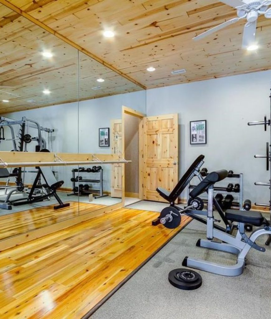 Rustic home gym with ceiling fan and hardwood floors.