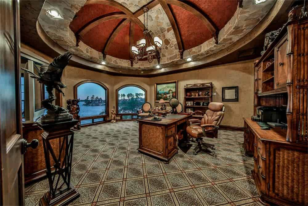 Mediterranean home office with stone and beam tray ceiling, chandelier, arched picture windows, a freestanding desk and carpet flooring.