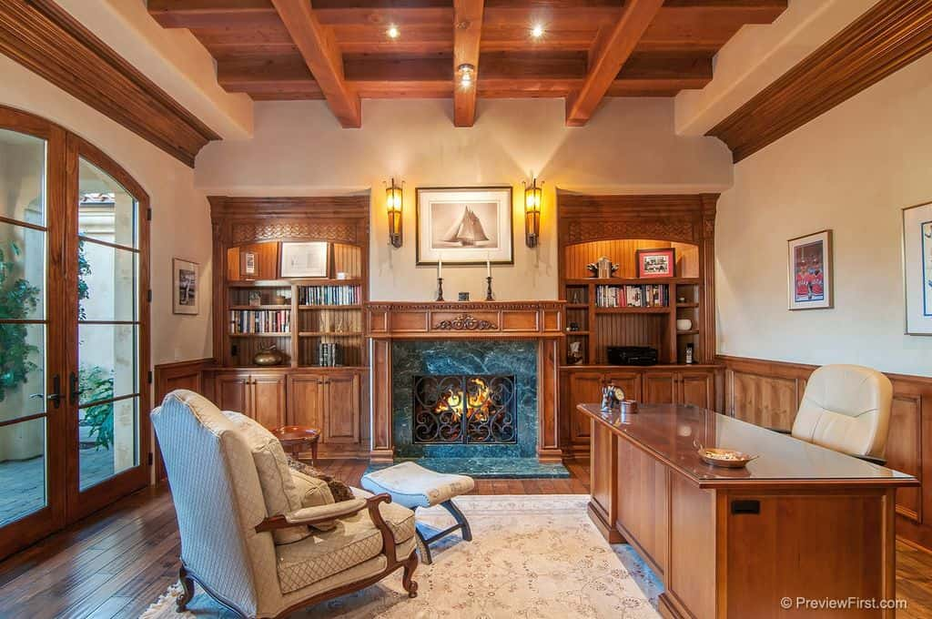 Mediterranean home office with beam ceiling, wall sconces and a fireplace flanked by built-in shelving.