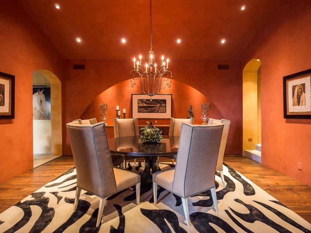 Spacious orange living room featuring a round dining table for 6, set on a zebra rug lighted by a chandelier and recessed lights.