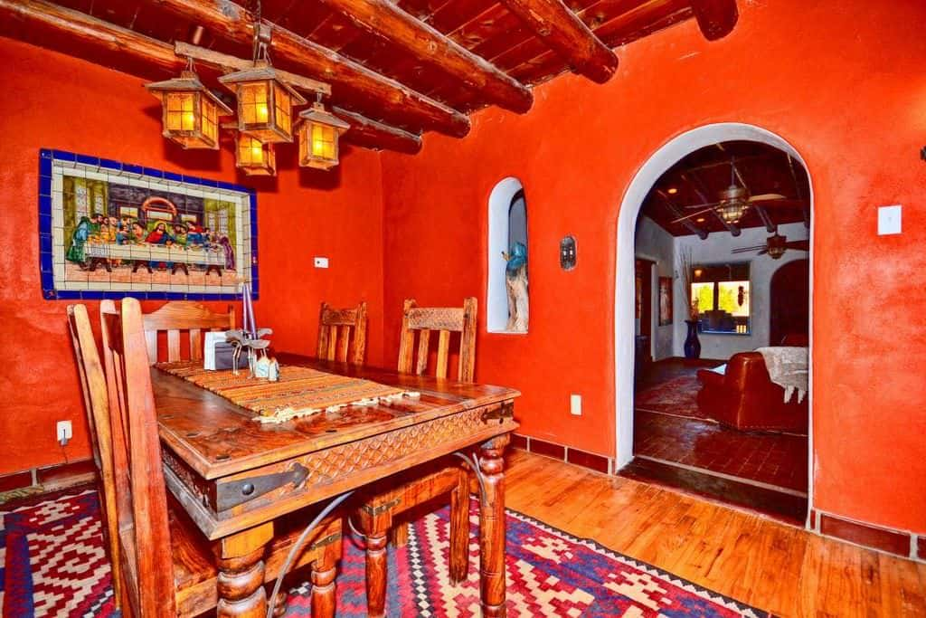 Southwestern orange dining room with ceiling with beams and hardwood floor.