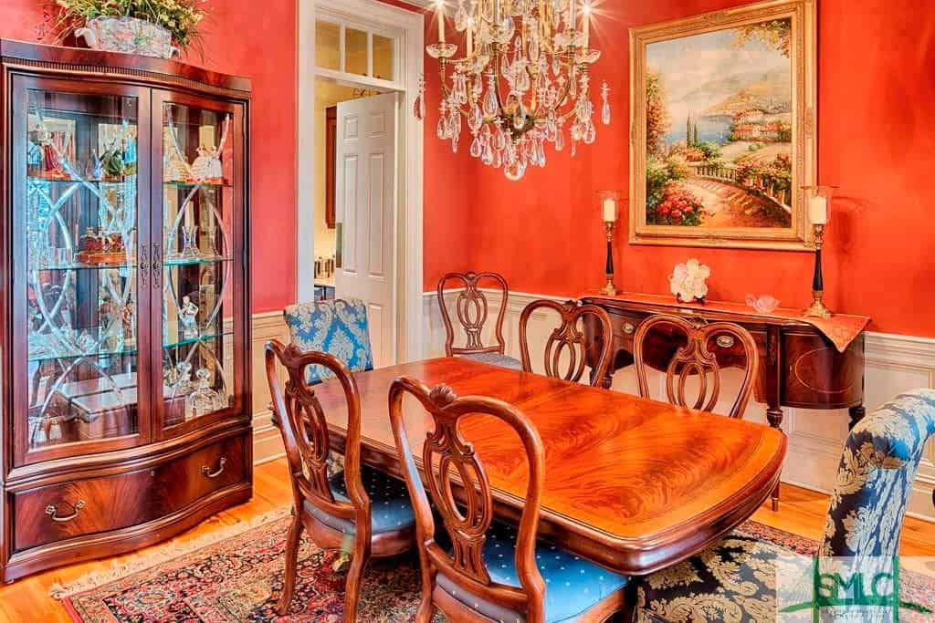 Traditional dining room with chandelier, wooden table, and freestanding shelf.
