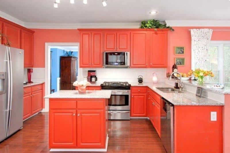 This kitchen features orange cabinetry and a hardwood flooring. Marble countertops spread across the kitchen. There's a small center island and a peninsula.