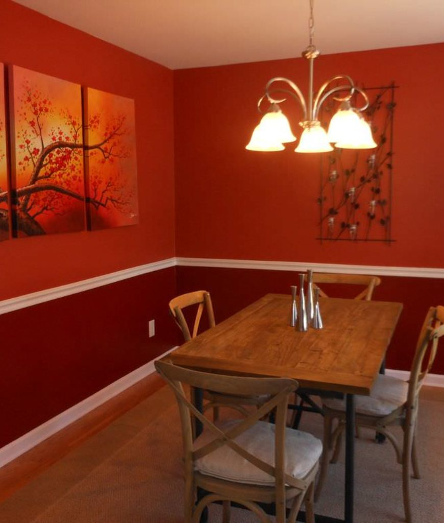 Eclectic red dining room with chandelier and rectangular wooden table.