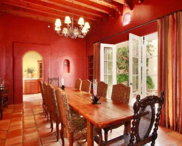 Mediterranean red dining room with rectangular wooden table and chandelier.