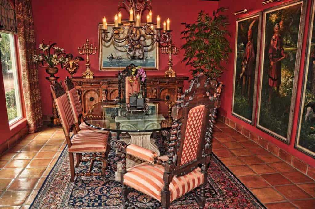 Elegant red dining room with large portraits on the wall as decorations. The room is lighted by a glamorous chandelier.