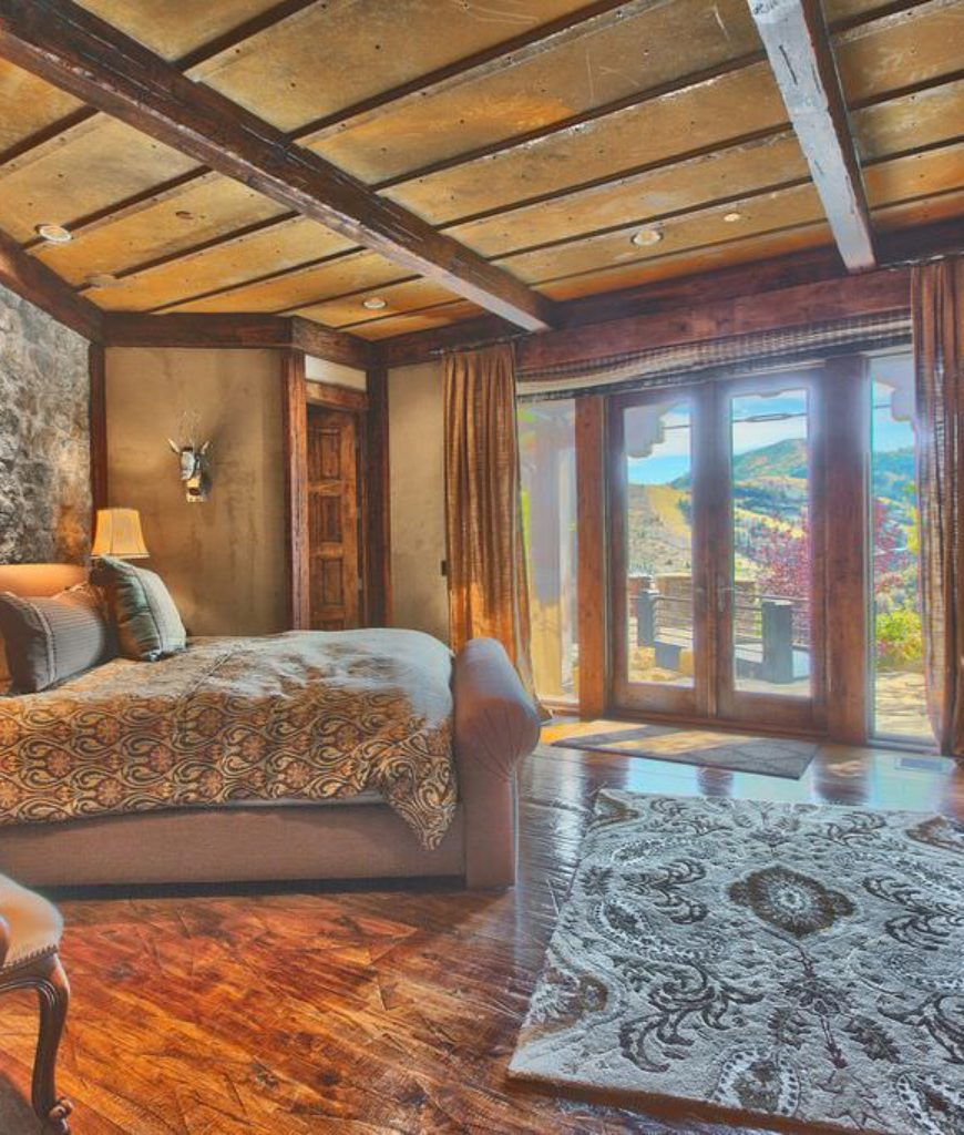 Rustic elegant bedroom with stone fireplace, stone wall and wood floors.