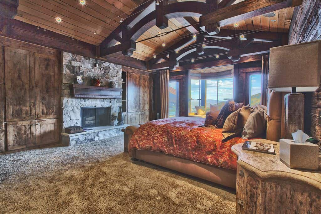 Rustic dark toned large master bedroom with carpeted floor, wood ceiling, wood walls, arc wood beams and limestone fireplace.