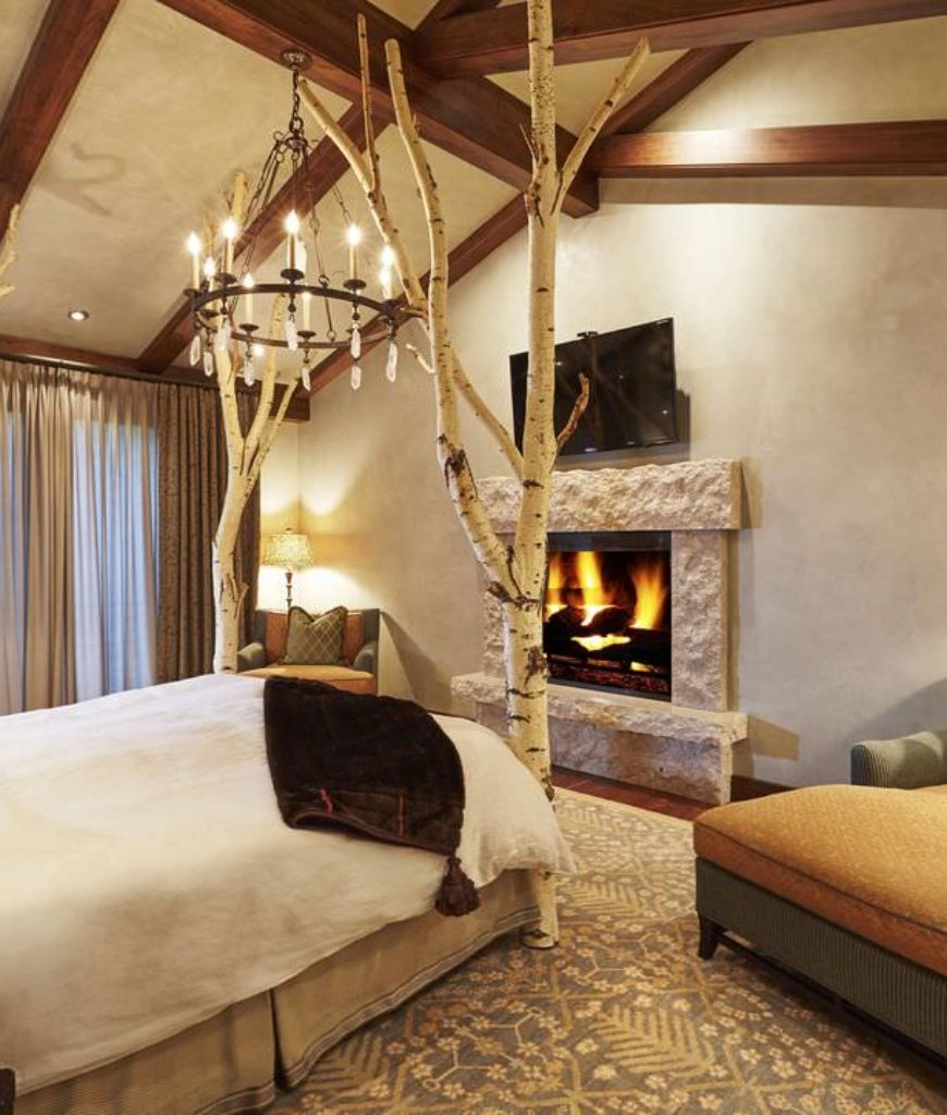All of the reclaimed trees, branches, furnishings and fireplace give this beige master's bedroom a cozy, rustic feel.