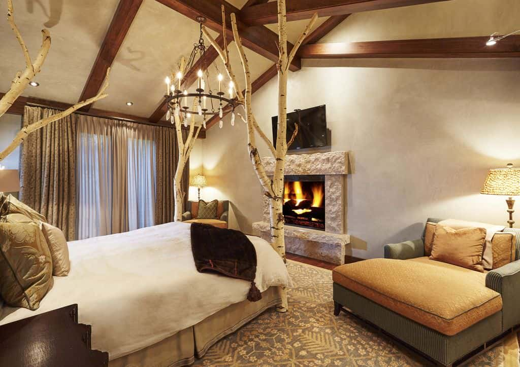 Rustic primary bedroom boasts a marvelous tree bed illuminated by a wrought iron chandelier that hung from the wood beam ceiling. It faces the stone fireplace in between chaise sofas.