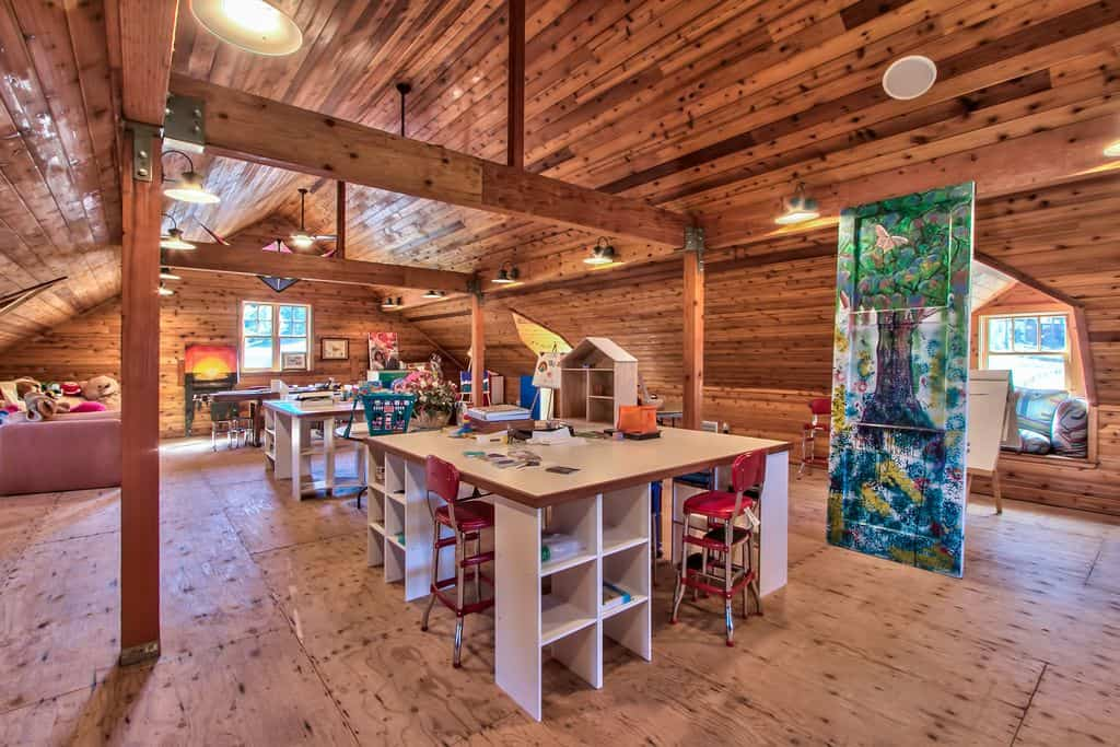 Rustic craft room for kids with beam ceiling and wall lights.