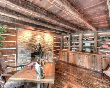 Rustic home office with wooden floor and ceiling with beams.
