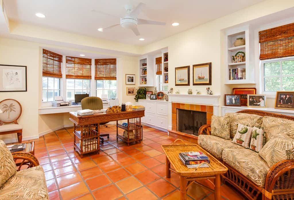 Mid-sized Tropical home office with ceiling fan light, wicker blinds, rattan tables and chairs, built-in desk, built-in shelving, a standard fireplace and terracotta tile flooring.