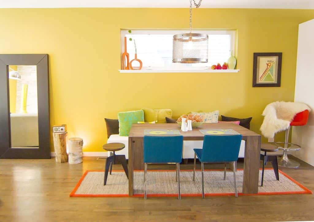 Small eclectic yellow dining room with built-in shelving, bench seating and hardwood flooring with a rug.