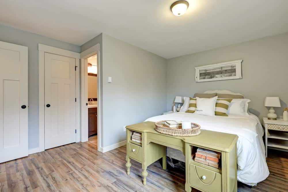 This guest bedroom is furnished with white nightstands and a comfy bed accented with a striped green pillow that complements with the desk on its end.