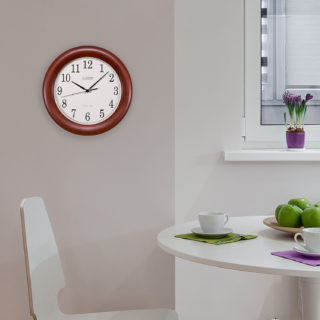 Classic round wall clock with wooden frame and manual time setting option.