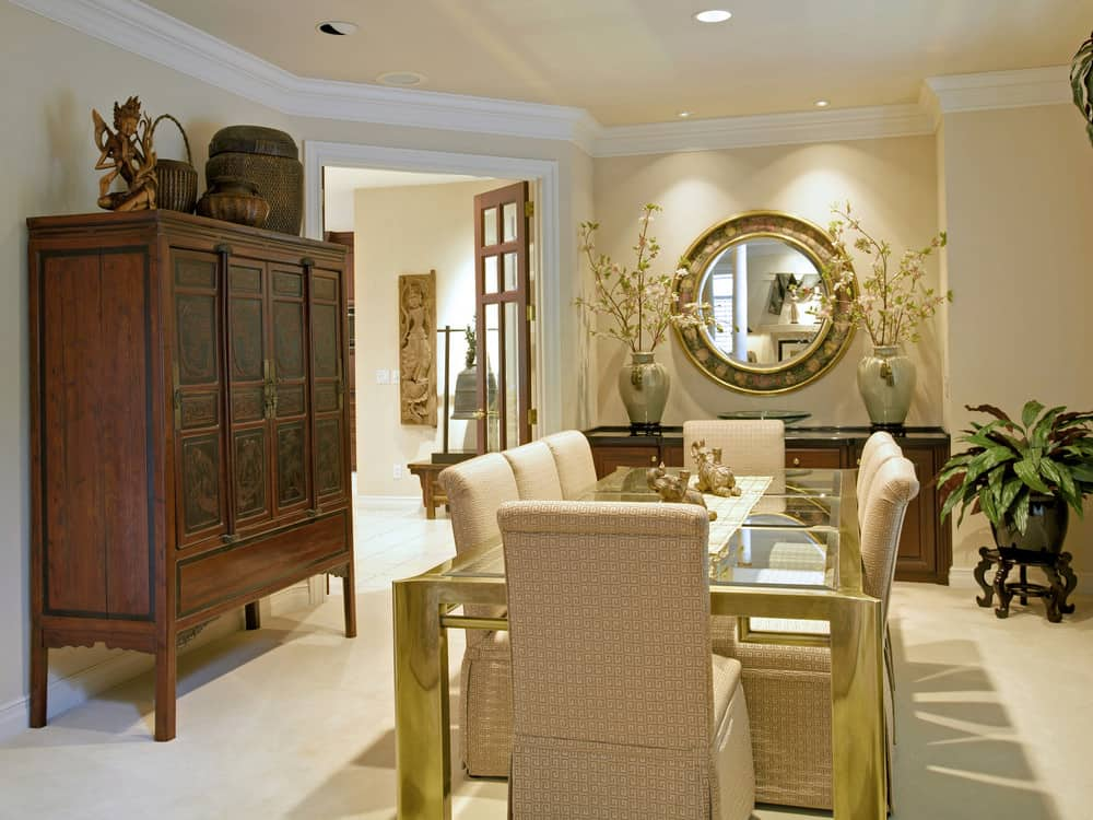 Gorgeous round mirror mounted on the beige wall creates a nice accent in this dining room. It also complements the glass top dining table that's lined with a plaid runner and surrounded by skirted chairs.