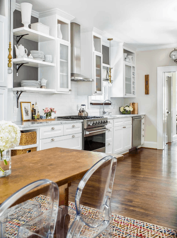 Eclectic kitchen with white walls and cabinets along with hardwood flooring and table.