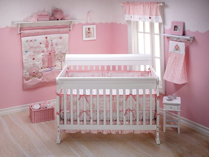 Pink baby girl crib with comforter and fitted sheet.