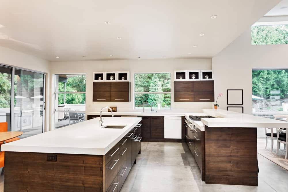 This cozy kitchen offers smooth white counters. The center island is a large and long one. There's a coffee spot on the side while the dining nook is on the other side.