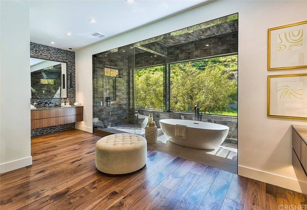 Large primary bathroom featuring hardwood flooring. There's a freestanding tub set near the window overlooking the beautiful garden area of the property. There's a walk-in shower on the corner as well.