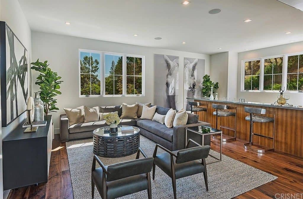 This home features a modern living room and a bar combo set on the hardwood flooring.