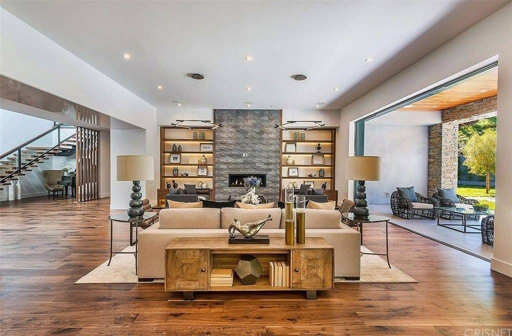 Another living room of Kris Jenner features a stylish fireplace and a nice living room set in a hardwood flooring.