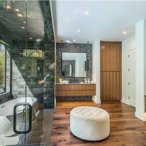 A bathroom perfect for the female-stacked family. This bathroom is so wide that it has a large dressing room and features a very stylish freestanding bathtub in a room separated by a huge glass door.