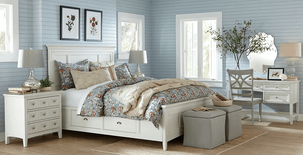 Country bedroom with light blue walls and hardwood flooring.