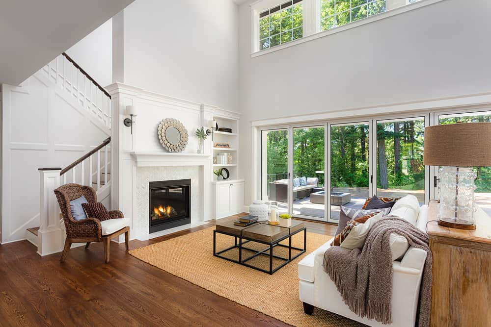 This home boasts a beautiful living space with hardwood flooring and a classy rug. There's a fireplace in front of the white sofa set. The high ceiling adds elegance to the home.