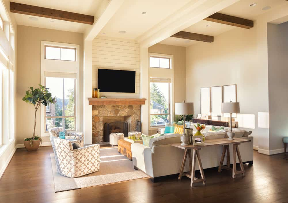 Large formal living room featuring white walls and a high ceiling along with the hardwood flooring. The sofa set looks perfect together with the fireplace.