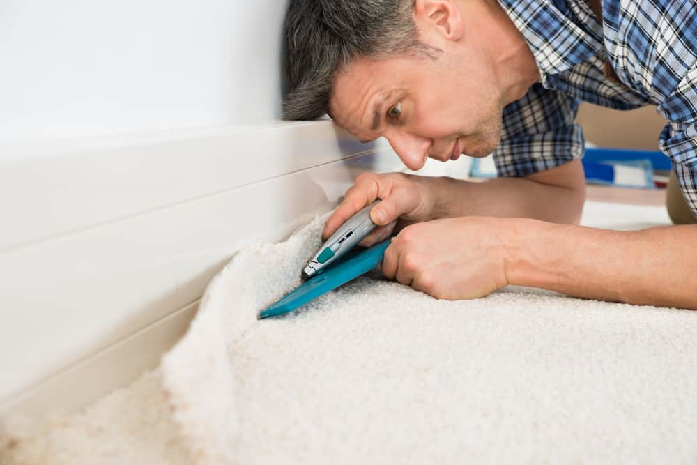 Man installing carpeting
