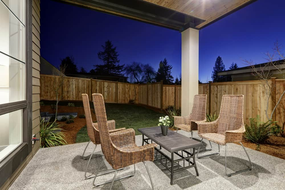 A modish patio featuring stylish seats and a piece of center table near the lawn area.