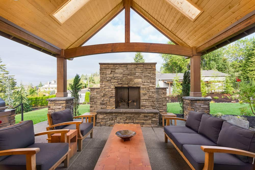 Large covered patio with enchanting sofa set with cushion seats and foam backrests along with a fireplace.