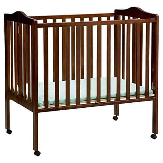Stylish portable mini crib with cherry finish and two position mattress height adjustment.